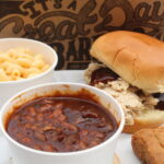 A barbeque sandwich, bowl of macaroni and cheese, bowl of baked beans, and a blondie dessert.